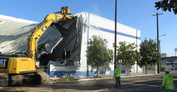 Workers demolish the closed Del Monte plant to make way for a future train station.